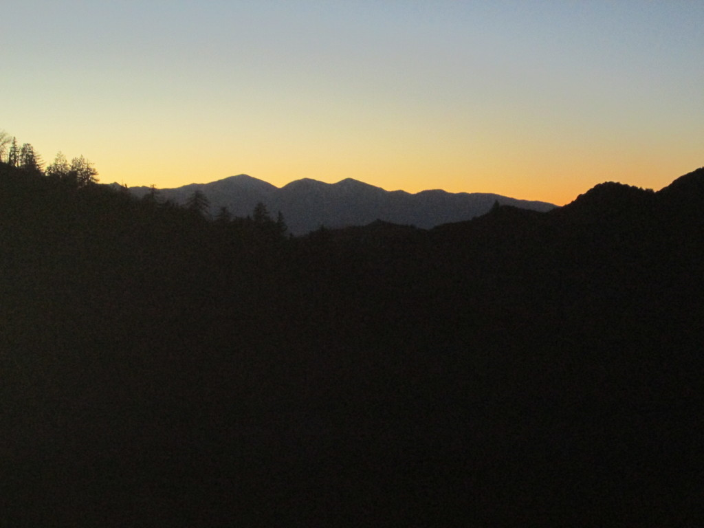 The silhouette of Mount Baldy can be view against the orange hued sunset.